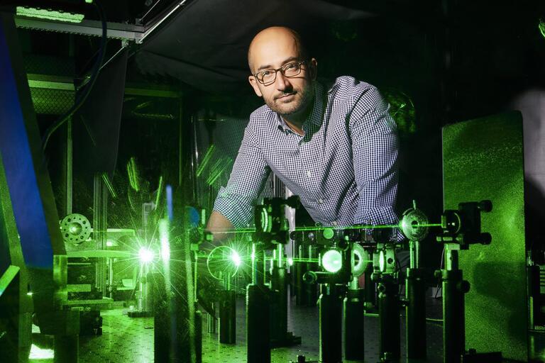 Ashkan Salamat standing behind an array of green lasers