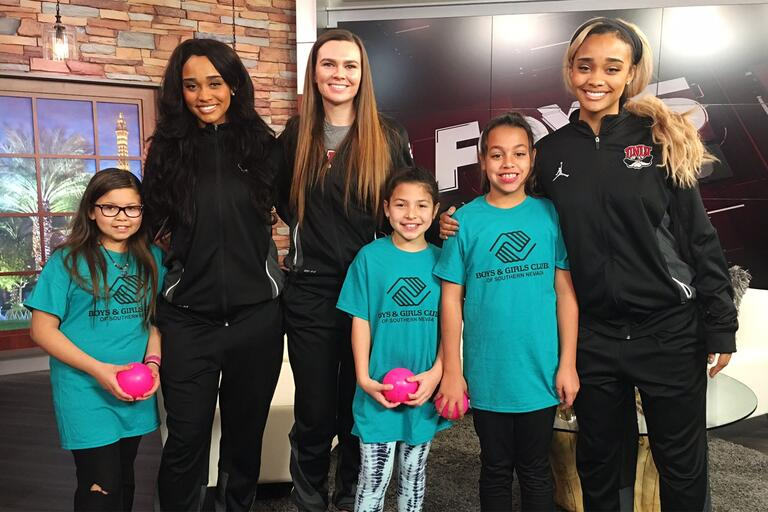 Student athletes pose with children from Boys and Girls club