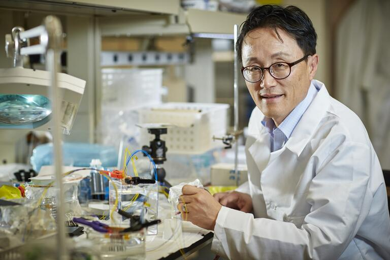 Kwang Kim sitting near a microscope