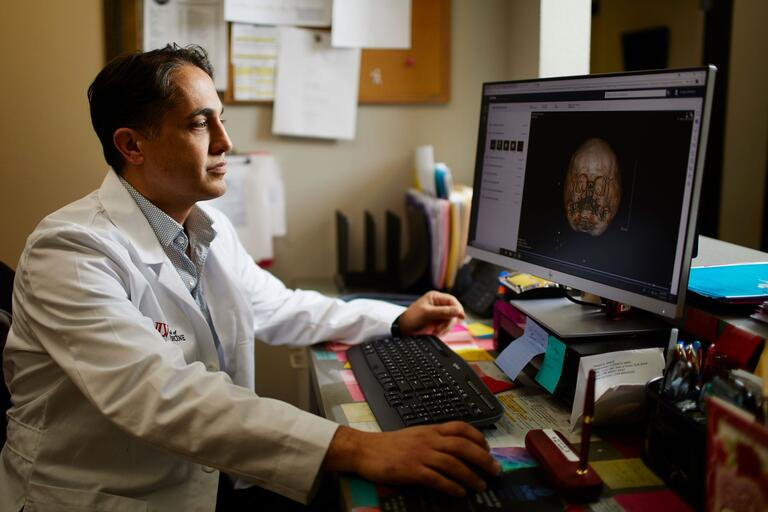 Dr. Menezes in U-N-L-V Medicine coat sitting at a desk looking at the screen with a medical image.