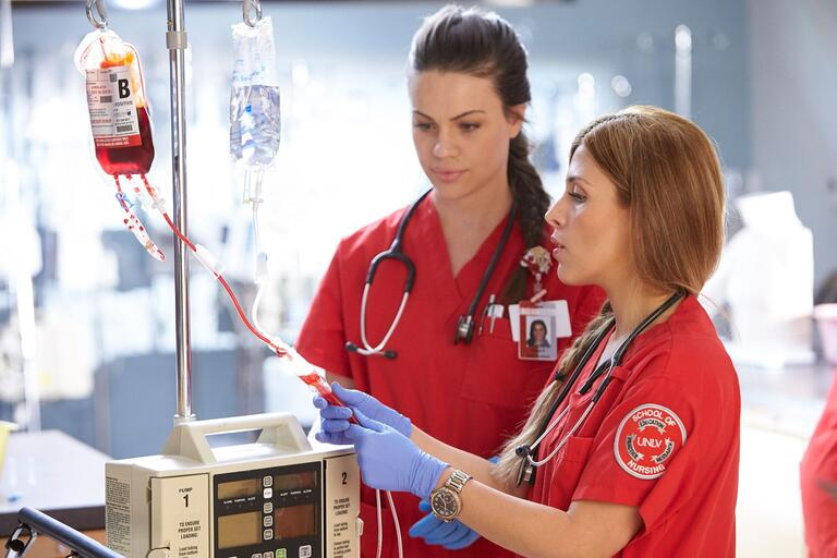 Two nursing students in red scrubs work with an IV in the SIM lab