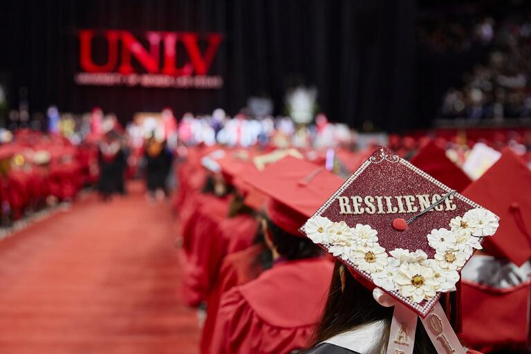 U-N-L-V commencement ceremony with many graduates in attendance, one graduation cap is in focus and is decorated with the word resilience