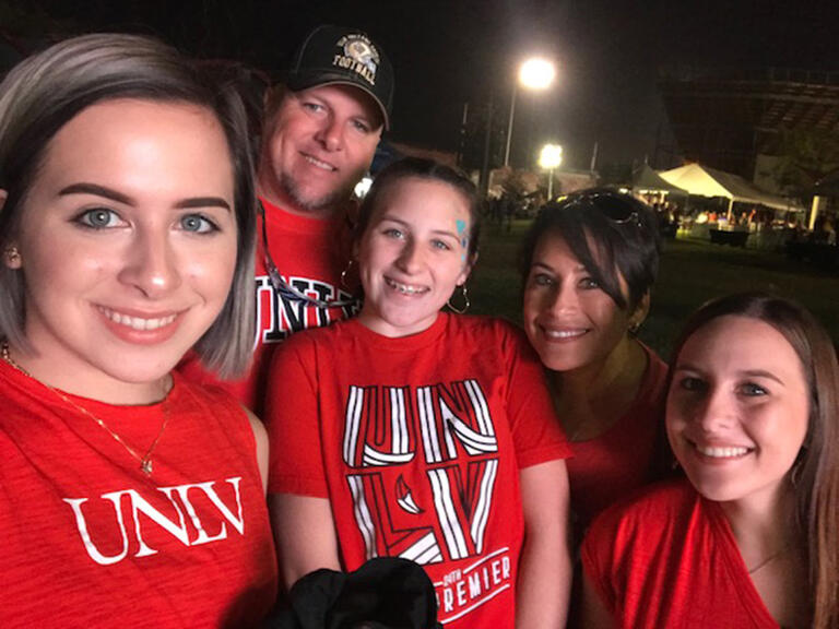 Photo of family in UNLV t-shirts outside at night