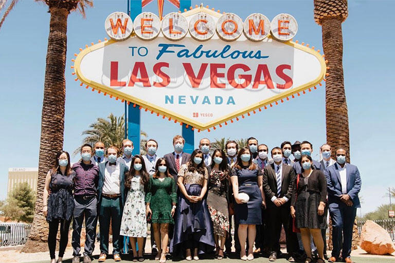 Group of people smiling in front of the famous Welcome to Las Vegas sign