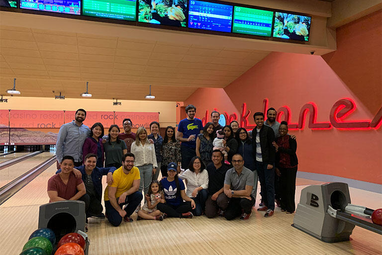 Group of people smiling in a bowling alley