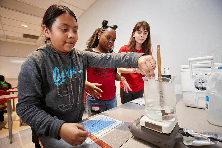 Three girls conducting an experiment