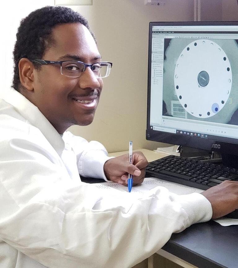 Male student smiling in front of a computer