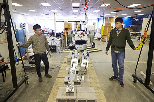 Members of DRC-HUBO at UNLV team working on a robot