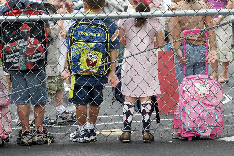 children lean against chain-linked fense with backpacks