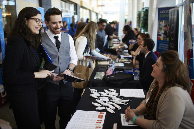 Two UNLV students speak with a potential employer at a job fair on campus.