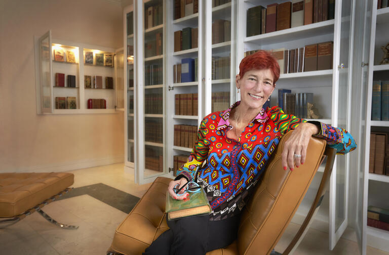 Beverly Rogers seated in home library