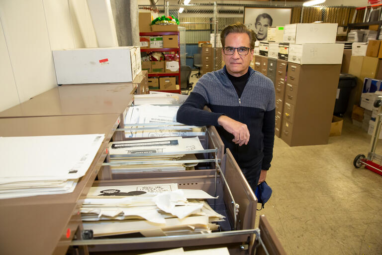 Artist Mike Smith standing next to file cabinets filled with his art