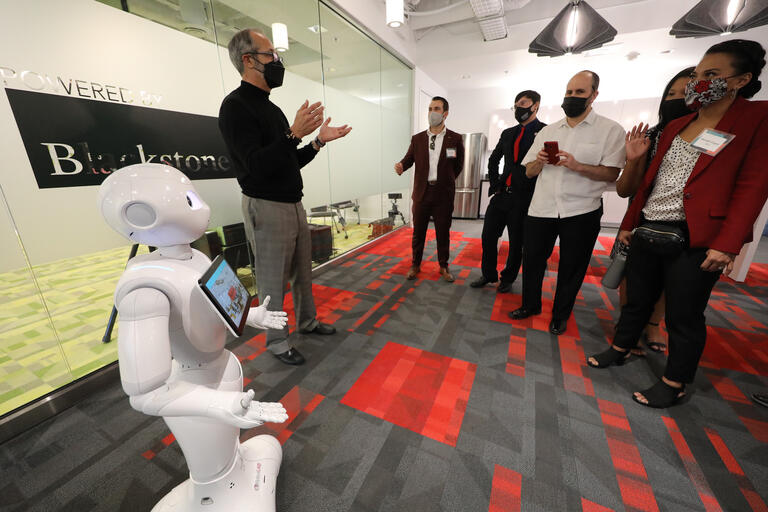 Professor, standing next to humanoid robot, leading a tour of office space