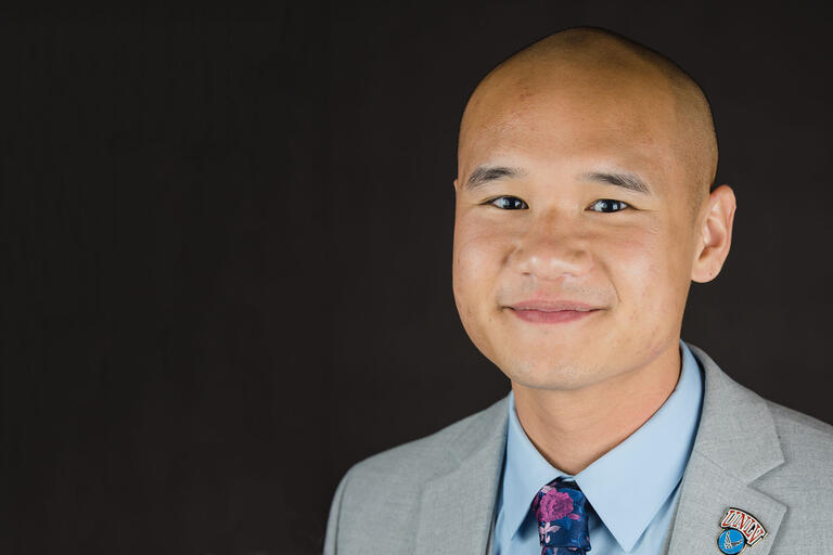 Portrait of Andrew Ho wearing a suit and tie and a UNLV pin
