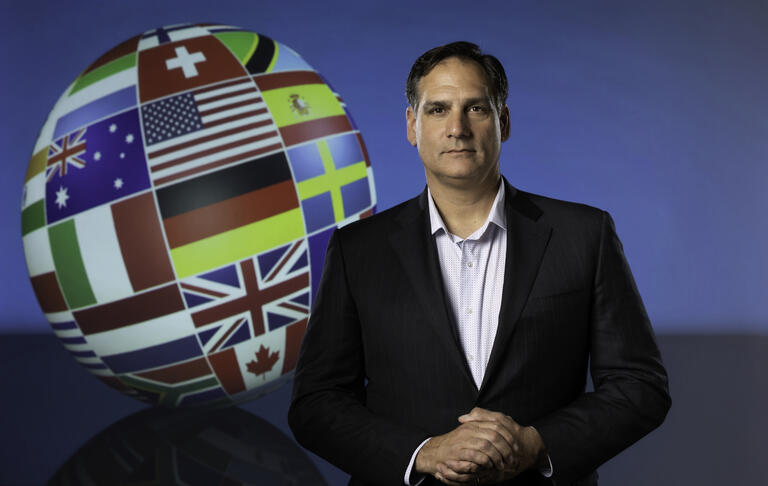 Man standing next to globe covered in different flags
