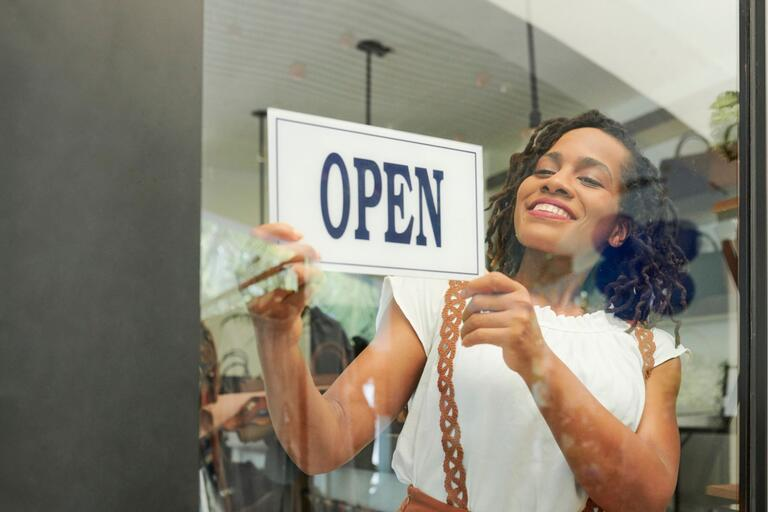 "smiling black woman hangs ""open"" sign on the window of her business"
