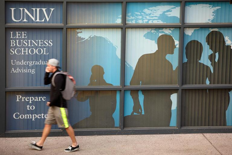 student walking by windows in front of business school advising center