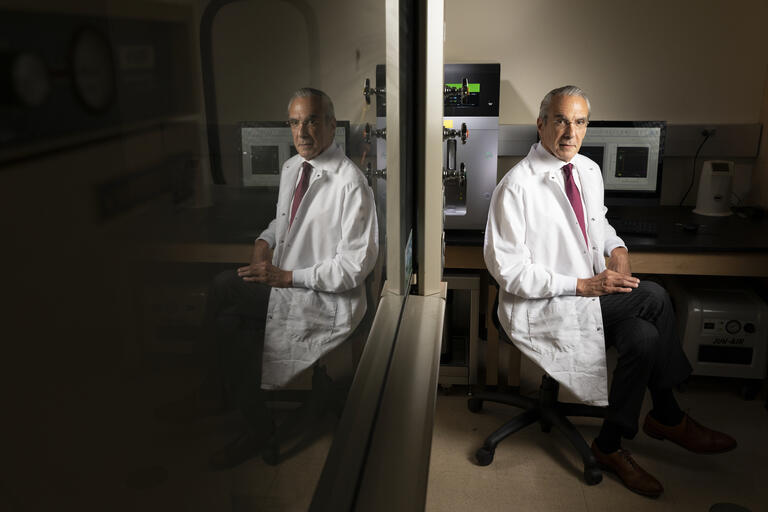 Dr. Jeffrey Cummings is pictured in a white lab coat in his lab, with his image reflected in a mirror