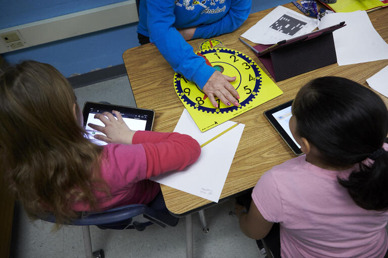 Two elementary school students and their principal sit around a desk with tablets, paper, and pencils