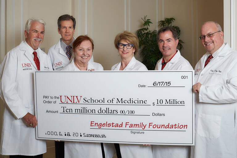 Bill Boldt, Mark Doubrava, Barbara Atkinson, Kris Engelstad McGarry, Len Jessup, and Kevin Page hold up giant check