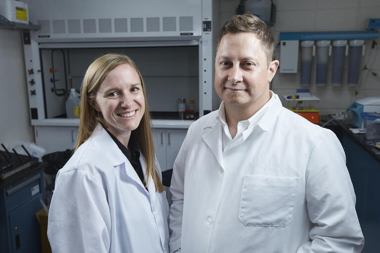 Rochelle and Dustin Hines standing in white lab coats