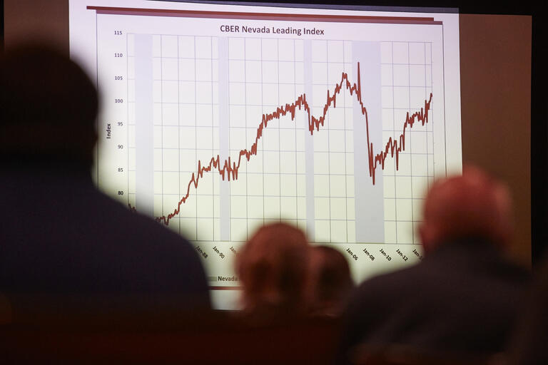 Image of economic chart projected on screen with onlookers