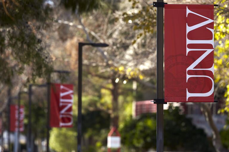Red UNLV banner with white letters hanging from light pole