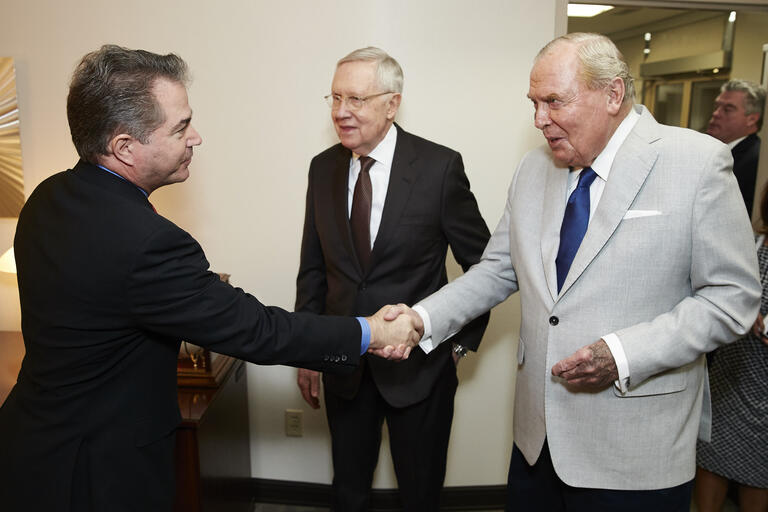 Len Dessup shakes hands with Jon Huntsman, Sr. with Sen. Harry Reid watching on