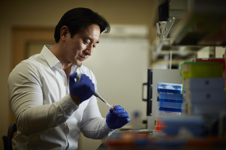 UNLV researcher Edwin Oh holds a pipette in his lab on campus
