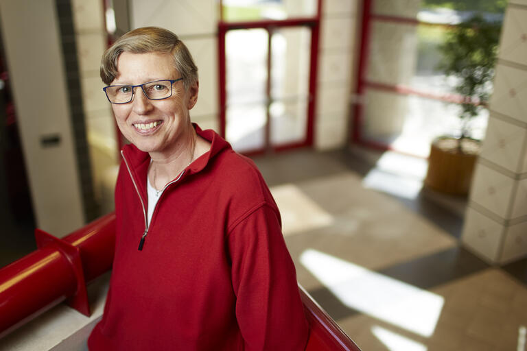 Gabriele Wulf is pictured in a red sweater standing on a landing in the lobby of the Bigelow Health Sciences on UNLV's campus