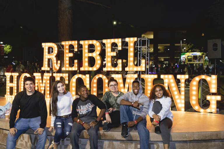 students pose in front of lighted sign that reads Rebel Homecoming