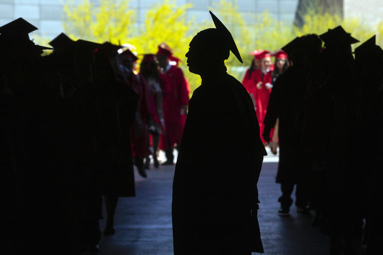 students in cap and gown line up for graduation ceremony