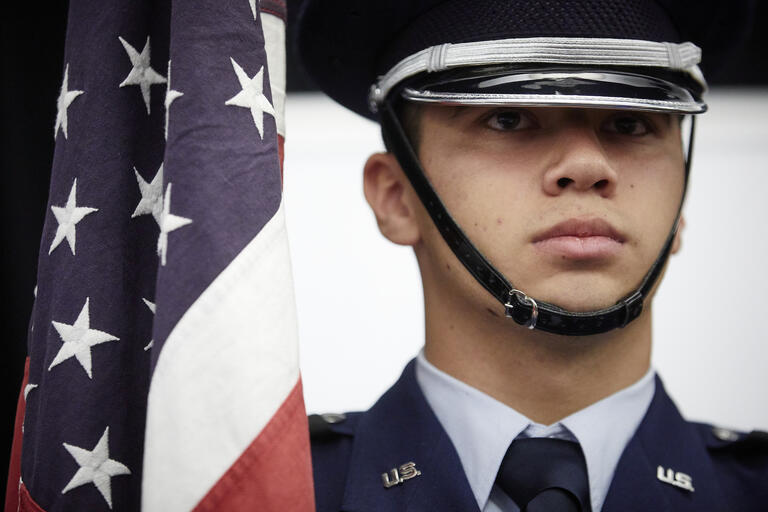 Air Force ROTC cadet standing next to American flag