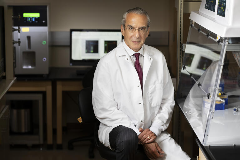 Jeffrey L. Cummings pictured in a white lab coat in his lab on UNLV's campus