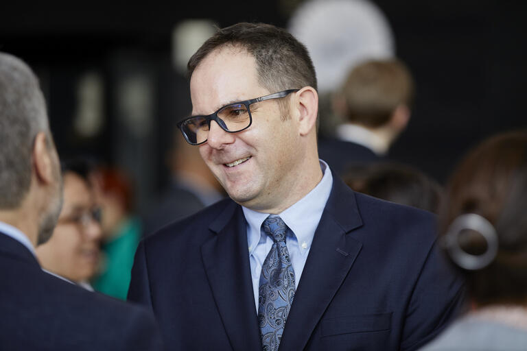 image of Dave Damore in suit during conversation at a reception