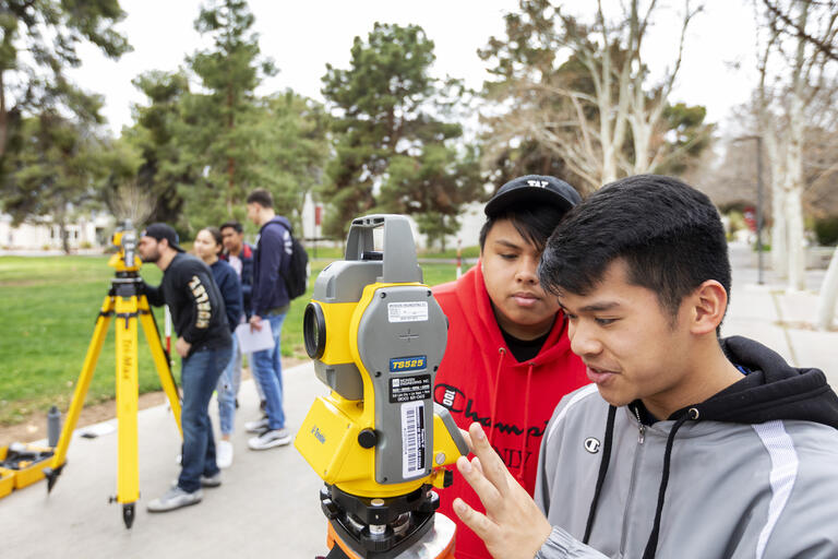 Students use a surveying instrument during a class on UNLV's campus