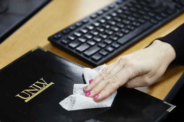 A hand is seen wiping a folder with a UNLV logo