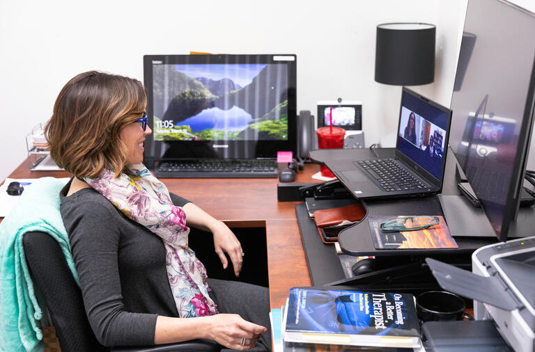 Michelle Paul, director of The PRACTICE Mental Health Clinic at UNLV, sits in front of her computer in her office to conduct a virtual meeting.