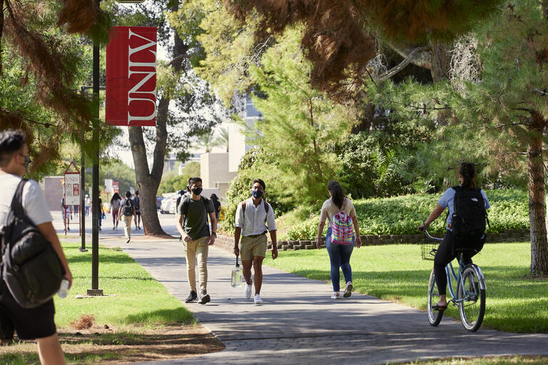 Students walking on campus on sunny day