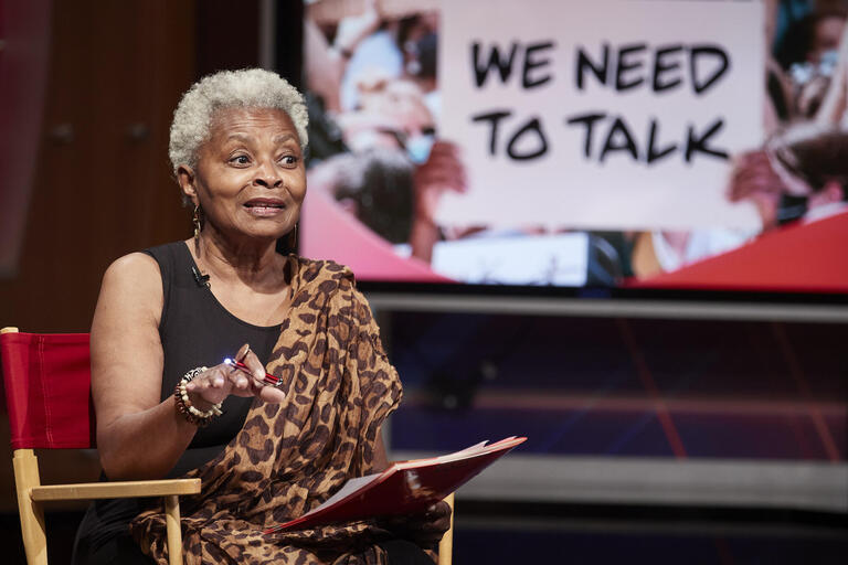 """Claytee White seated with """"We Need to Talk"""" on TV screen behind her"""