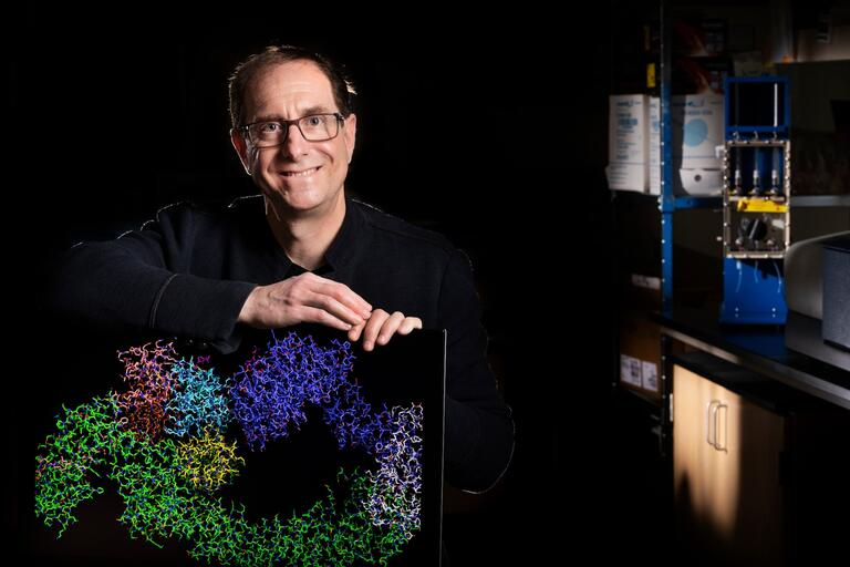 Gary Kleiger sits in his lab with a computer monitor showing a colorful protein complex