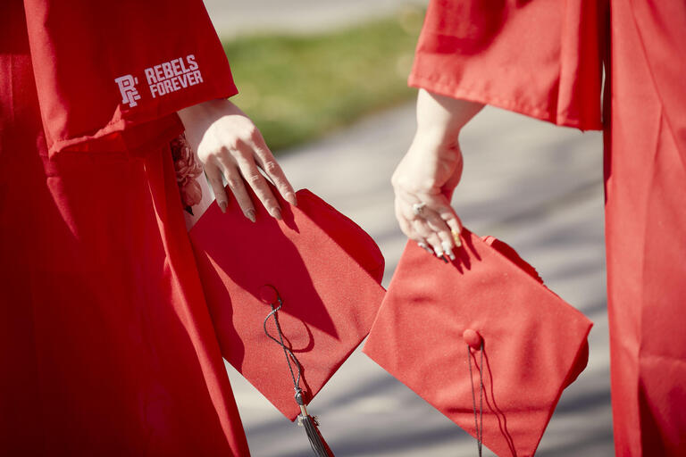 A close-up image of two UNLV grads holding their red UNLV mortarboards for commencement photos on campus