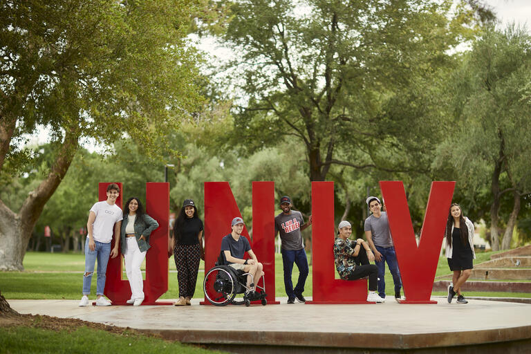 UNLV students outdoors standing amidst large red UNLV letters