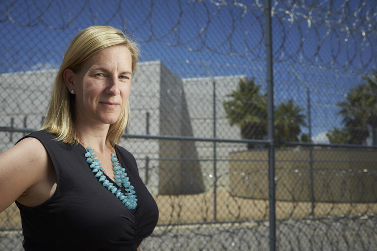 A portrait of UNLV associate professor Emily Salisbury standing in front of the Florence McClure Women's Correctional Center.