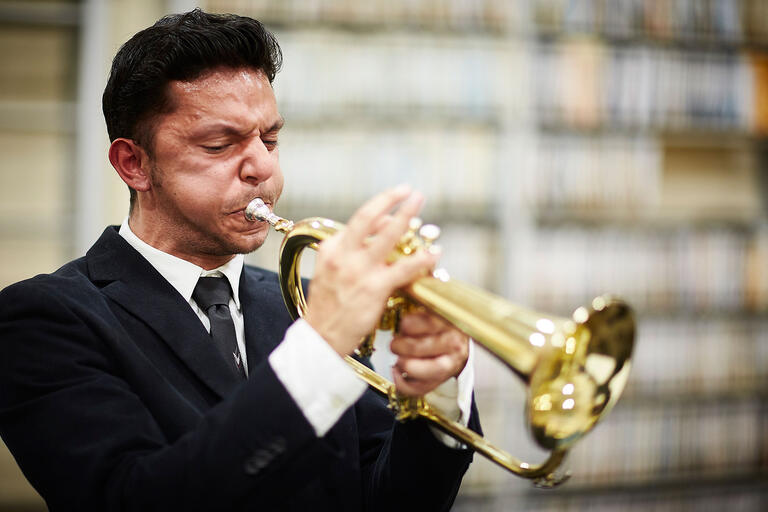 Young man wearing a black suit playing a trumpet