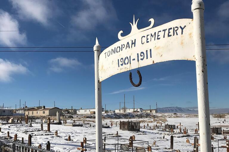"""Cemetary with sign that reads """"Tonopah Cememtary 1901-1911."""""""