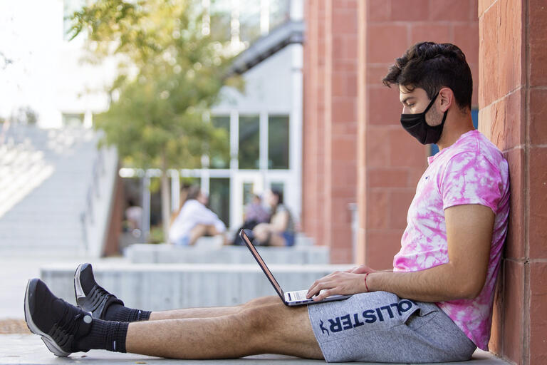student wearing face covering sits on ground, using laptop