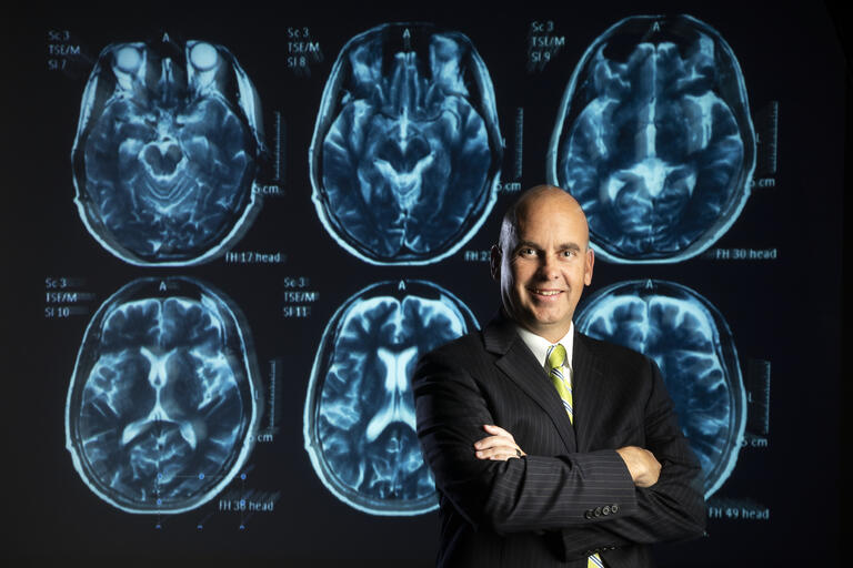 A portrait of Jefferson Kinney in front of a brain scan.