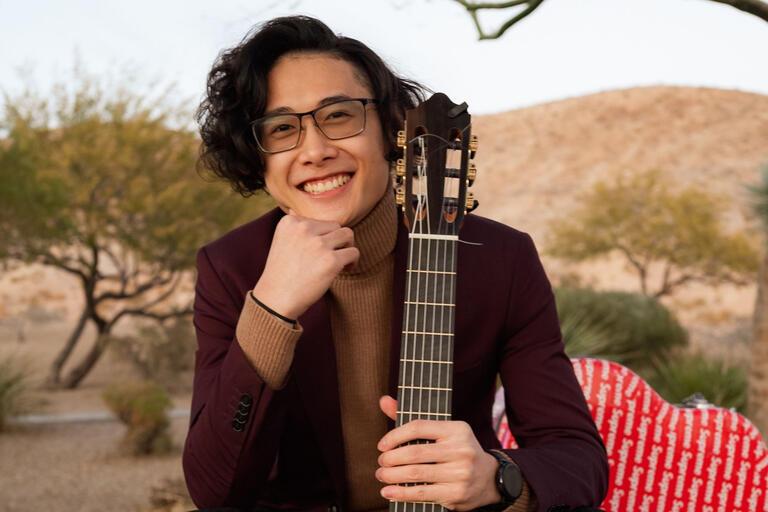 A man holds a guitar