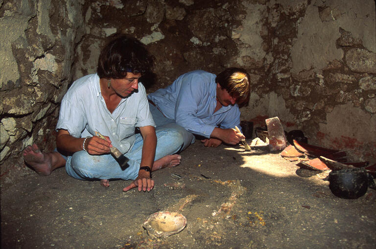 A photo of UNLV archaeologists Diane and Arlen Chase examining items on the floor of a tomb in Caracol, Belize.